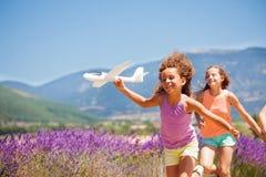 跑与飞机模型的愉快的女孩户外 库存照片