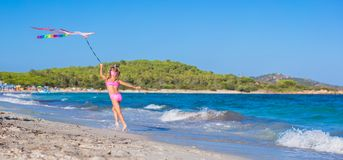 跑与飞行风筝的小愉快的女孩  免版税库存照片