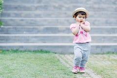 跑为乐趣的小女孩在庭院里 库存照片