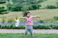 跑为在庭院里的小女孩 库存图片