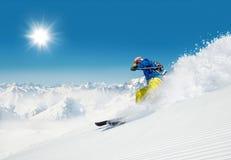 跑人的滑雪者下坡 免版税库存图片