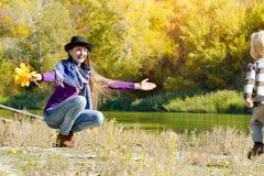跑儿子的妈妈抓住 秋天,一个晴天 河岸 免版税库存照片