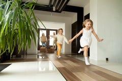 跑入房子,移动的天的激动的孩子在新的家 免版税库存图片
