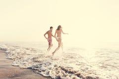 跑入水的愉快的夫妇 免版税库存图片