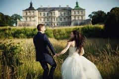 跑到城堡的新娘和新郎 免版税库存照片