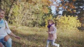 跑到妈妈的愉快的女孩在秋天公园 影视素材