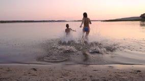 跑到河的两个孩子在日落,慢动作 股票录像