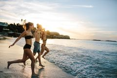 跑到海的小组愉快的朋友 免版税图库摄影