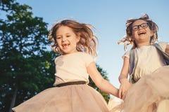 跑反对日落的两个快乐的女孩 免版税库存图片