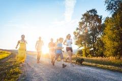 跑和使用在夏天风景的一条道路的嬉戏的家庭 免版税库存照片