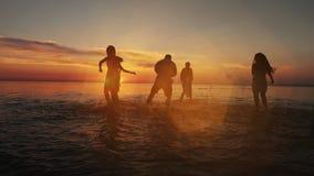 跑和使用在水中的小组愉快的女孩在日落的海滩 的秀丽和获得快乐的少年的朋友乐趣 影视素材