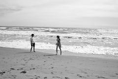跑和使用在海前面的beatch的男孩和女孩 Sepi 免版税库存照片