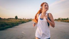 跑和听到在耳机的音乐的妇女 库存图片