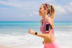 跑和听到在耳机的音乐的微笑的女孩 免版税库存图片
