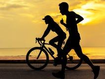 跑和循环在海滩的人们 免版税库存图片