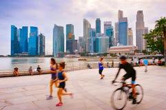 跑和循环新加坡的人们 免版税库存图片