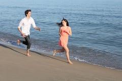 跑和挥动在海滩的少年夫妇  免版税库存图片