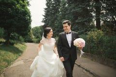 跑和跳跃在公园的新婚的夫妇,当握手时 免版税图库摄影