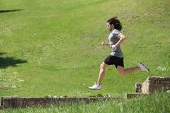 跑和跳跃在公园的运动员 免版税库存照片