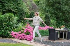 跑和跳跃在欧洲庭院里的愉快的美丽的年轻studient女孩 她查看照相机 库存图片
