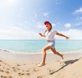 跑和跳跃在海滩的滑稽的小女孩 图库摄影