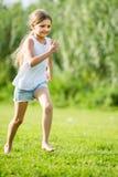 跑和跳跃在草的女孩 免版税库存图片