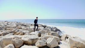 跑和跳过在一个海滩的岩石的年轻适合的运动员与击中峭壁和水飞溅的强的海浪 股票视频