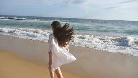 跑和转动在海滩的愉快的妇女在海洋附近 年轻美丽的女孩享有生活和获得乐趣海上 股票视频