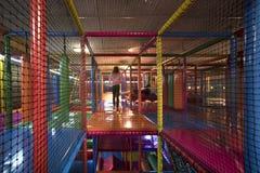 跑在一个五颜六色的室内操场里面的孩子 库存图片