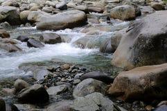 跑在一个多岩石的海滩下的小河水 图库摄影