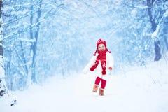 跑在一个多雪的公园的小女孩 免版税库存照片