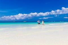 跑在一个热带海滩的新娘和新郎 库存照片