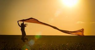 跑在一条农村路的少妇在夏天领域的日落 生活方式炫耀自由背景 免版税库存图片