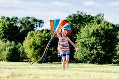跑在与一只五颜六色的风筝的草地的愉快的女孩 免版税库存图片