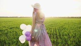 跑在与五颜六色的气球的春天领域的秀丽女孩 影视素材
