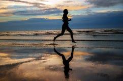 跑在与反射的日落海滩的妇女慢跑者剪影 免版税库存照片
