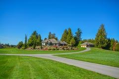 跑在与大农夫的房子的风景的柏油路连接点小山的 免版税库存照片