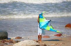 跑在与大颜色风筝的领域的女孩 图库摄影