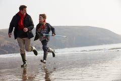 跑在与捕鱼网的冬天海滩的父亲和儿子 库存照片
