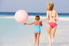 跑在与气球的美丽的海滩的母亲和女儿 库存照片