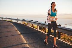 跑在乡下公路的愉快的少妇 免版税库存图片