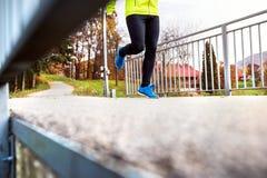 跑在五颜六色的秋天自然的公园的年轻运动员 库存图片