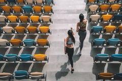 跑在体育场台阶的两个女运动员 库存照片