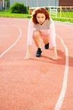 跑在体育场的美丽的红发女孩 免版税库存图片
