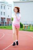 跑在体育场的美丽的红发女孩 图库摄影