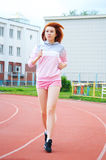 跑在体育场的美丽的红发女孩 免版税库存照片