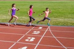 跑在体育场轨道、训练和儿童健身的家庭体育、母亲和孩子 免版税库存图片
