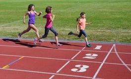 跑在体育场轨道、训练和孩子的家庭健身、母亲和孩子炫耀健康生活方式 免版税库存照片
