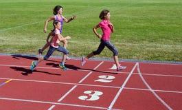 跑在体育场轨道、训练和孩子的家庭健身、母亲和孩子炫耀健康生活方式 图库摄影