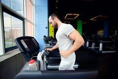 跑在健身俱乐部的一辆踏车的肌肉人 免版税库存照片